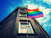Rainbow LGBT flag. Low angle view of a rainbow LGBT, Lesbian, Gay, Bisexual and Transgender flag outside a building royalty free stock photos