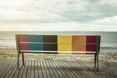 Rainbow LGBT pride flag painted on a wooden bench. On the beach with the sea in the background stock images