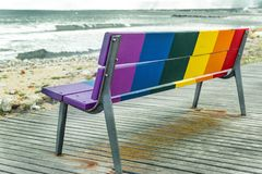 Rainbow LGBT pride flag painted on a wooden bench. On the beach with the sea in the background stock photo
