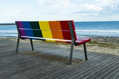 Rainbow LGBT pride flag painted on a wooden bench. On the beach with the sea in the background royalty free stock photography