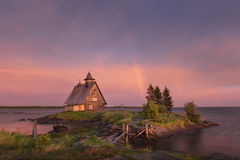 Rainbow on the lilac sky after a thunderstorm. Landscape of the White Sea with a small island, a wooden old house and a ruined bri. Rainbow after a severe storm Stock Images
