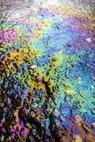 Rainbow Liquid Petrol Pollution Leak on Asphalt Road. Colourful liquid pattern spillage stock image