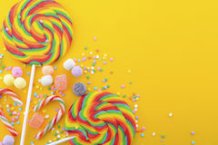 Rainbow lollipop candy on bright yellow wood table. Stock Photos