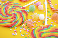 Rainbow lollipop candy on bright yellow wood table. Royalty Free Stock Photo