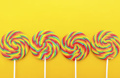 Rainbow lollipop candy on bright yellow wood table. Royalty Free Stock Images