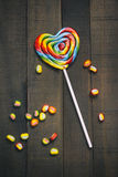 Rainbow Lollipop and marmalade on wooden background Royalty Free Stock Photography