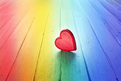 Rainbow Love Heart Background. A red love heart on a rainbow wood background