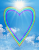 Rainbow love heart blue sky frame. A large empty rainbow shaped heart creating a frame on a blue sky background with a big bright sunburst positioned in the Stock Photography