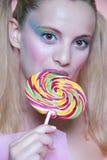 Rainbow makeup and swirl lollipop Stock Photo