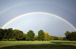 A rainbow with many shades of blue over a golf course. Shot was taking at full sun royalty free stock photos