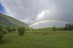 Rainbow in a mountain valley. Stock Image