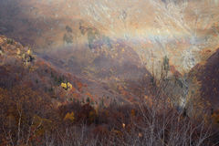 Rainbow in the mountain valley in the fall. Royalty Free Stock Photos