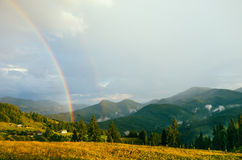 Rainbow in the mountain valley after rain. Beautiful landscape in Carpathians. Ukraine Royalty Free Stock Photos