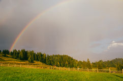 Rainbow in the mountain valley after rain. Beautiful landscape in Carpathians. Ukraine Stock Photo