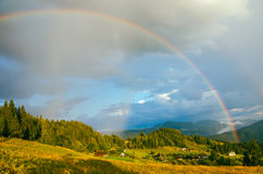 Rainbow in the mountain valley after rain. Beautiful landscape in Carpathians. Ukraine Royalty Free Stock Images