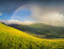 Rainbow in the mountain valley during rain Stock Images