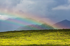 Rainbow in mountains Stock Images