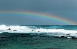 Rainbow on the ocean. In Guadeloupe, on the tip of the castles, in stormy weather, a beautiful rainbow over the ocean and big blue waves Royalty Free Stock Image