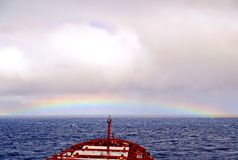 Rainbow in the ocean after rain and thunderstorms. Colorful views of the rainbow against the sky, clouds and sea horizon stock image