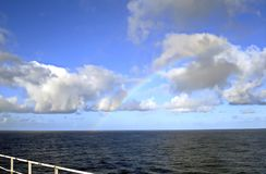 Rainbow in the ocean after rain and thunderstorms. Colorful views of the rainbow against the sky, clouds and sea horizon stock photo