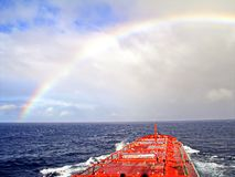 Rainbow in the ocean after rain and thunderstorms. Colorful views of the rainbow against the sky, clouds and sea horizon royalty free stock photography