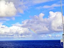 Rainbow in the ocean after rain and thunderstorms. Colorful views of the rainbow against the sky, clouds and sea horizon royalty free stock images