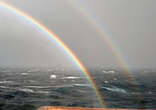 Rainbow in the ocean after rain and thunderstorms. Colorful views of the rainbow against the sky, clouds and sea horizon royalty free stock photos