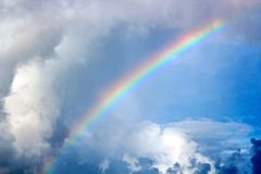Rainbow in the ocean after rain and thunderstorms. Colorful views of the rainbow against the sky, clouds and sea horizon stock images