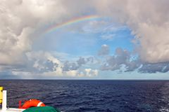 Rainbow in the ocean after rain and thunderstorms. Colorful views of the rainbow against the sky, clouds and sea horizon royalty free stock image
