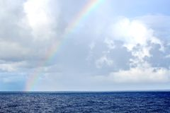 Rainbow in the ocean after rain and thunderstorms. Colorful views of the rainbow against the sky, clouds and sea horizon stock photography