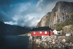 Rainbow ofer red houses rorbuer of Reine in Lofoten, Norway with red rorbu houses, clouds, rainy blue sky and sunny stock photo