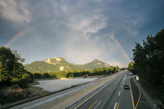 Rainbow over alp mountains and highway Royalty Free Stock Photo