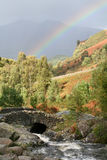 Rainbow over Ashness Bridge & Skiddaw. A brief moment where the sunshine from behind and the misty rain ahead combined to create this beautiful rainbow which Royalty Free Stock Photography