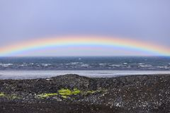 Rainbow over the atlantic ocean in iceland. Rainbow over the atlantic ocean during summer in iceland stock photography
