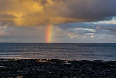 Rainbow over the Atlantic Ocean during sunset in Iceland stock photo