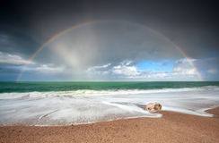 Rainbow over Atlantic ocean waves on coast Royalty Free Stock Photo