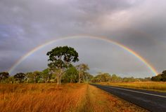 Rainbow over Australian country road. Early morning rainbow over an outback country road in Australia Royalty Free Stock Images