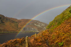 Rainbow over autumn fall water hills and mountains. Royalty Free Stock Photography