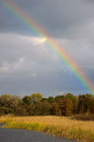 Rainbow over autumn forest. Multicolored rainbow shining over an autumn forest Royalty Free Stock Photography