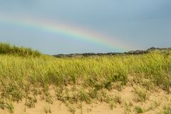 Rainbow over the Beach. A beautiful rainbow over dunes at a beach in Cape Cod Massachusetts royalty free stock images