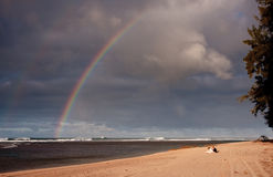 Rainbow over a broad sandy beach. Rainbow over a sandy beach with a couple in the foreground royalty free stock photos