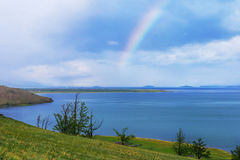 Rainbow over calm water of taiga lake Royalty Free Stock Photo
