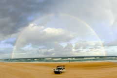 Rainbow over car on beach Royalty Free Stock Image