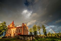 Rainbow over the church, dramatic stormy clouds