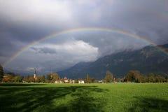 Rainbow over city of Interlaken, Switzerland. Scenery of town, summer, mountains and rainbow stock photo