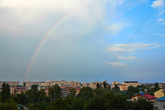 Rainbow over the city. A landscape with the city after the rain when the rainbow appears Royalty Free Stock Image