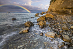 Rainbow over the cliff after passing an evening storm Stock Images