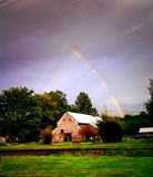 Rainbow over country barn Royalty Free Stock Images