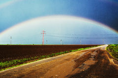 Rainbow over country road Royalty Free Stock Photo