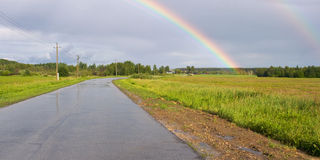 Rainbow over countryside road Stock Image